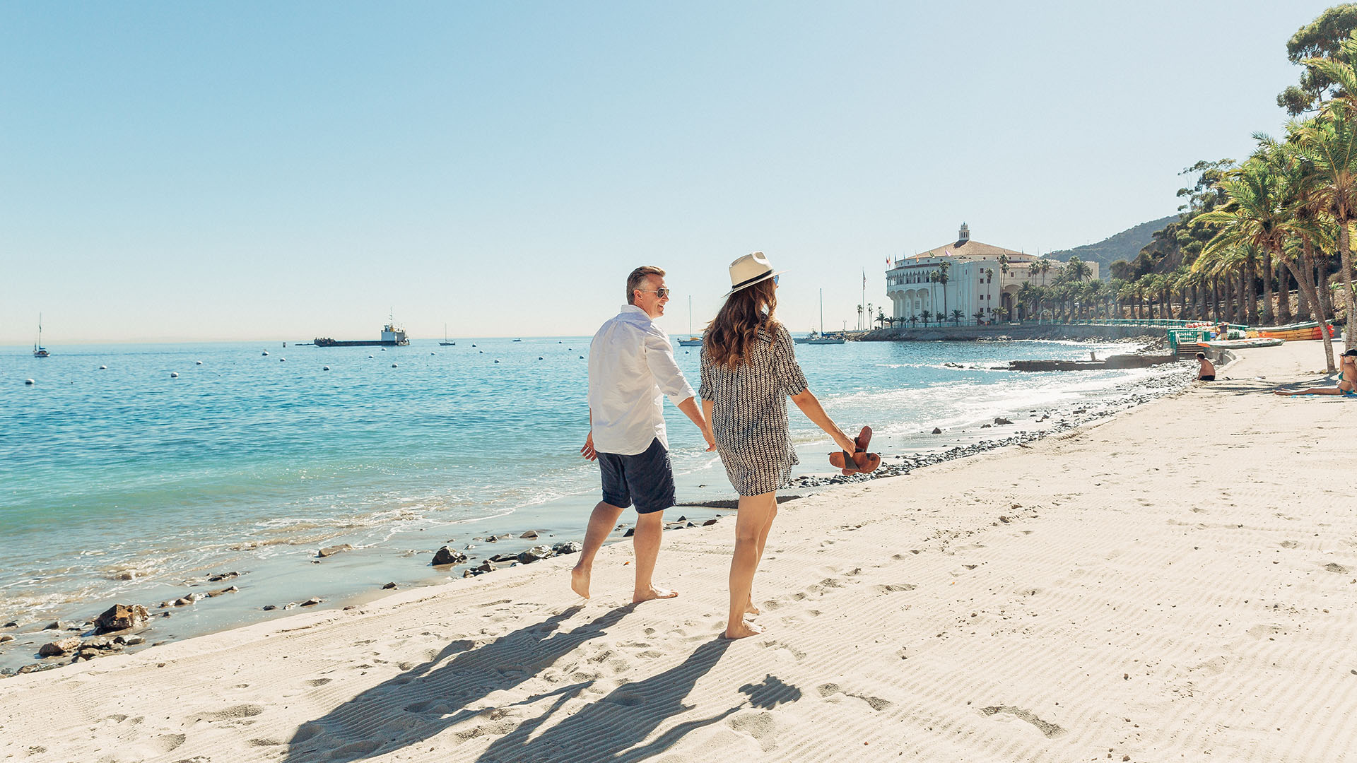 Couple walking on the beach with view of the Catalina Island casino in the background