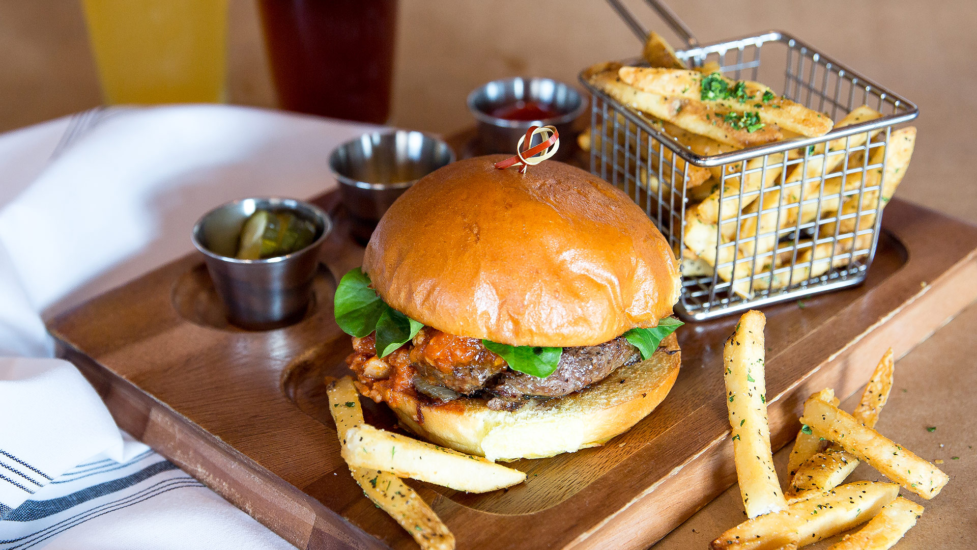 Burger and fries on wooden plate