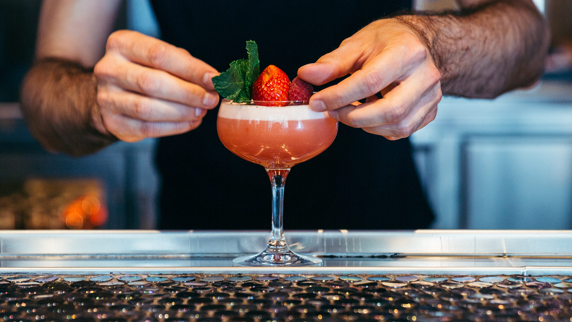 Hands finishing a cocktail with mint and berries