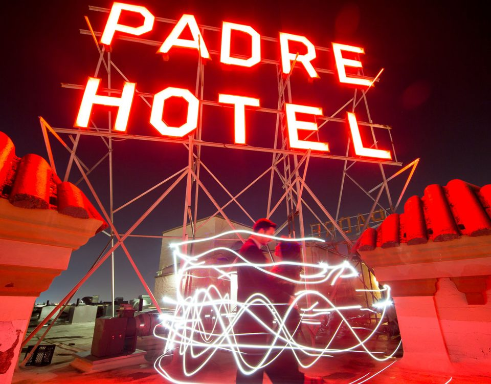 Padre sign on the rooftop at night with red glow and couple standing in front of them