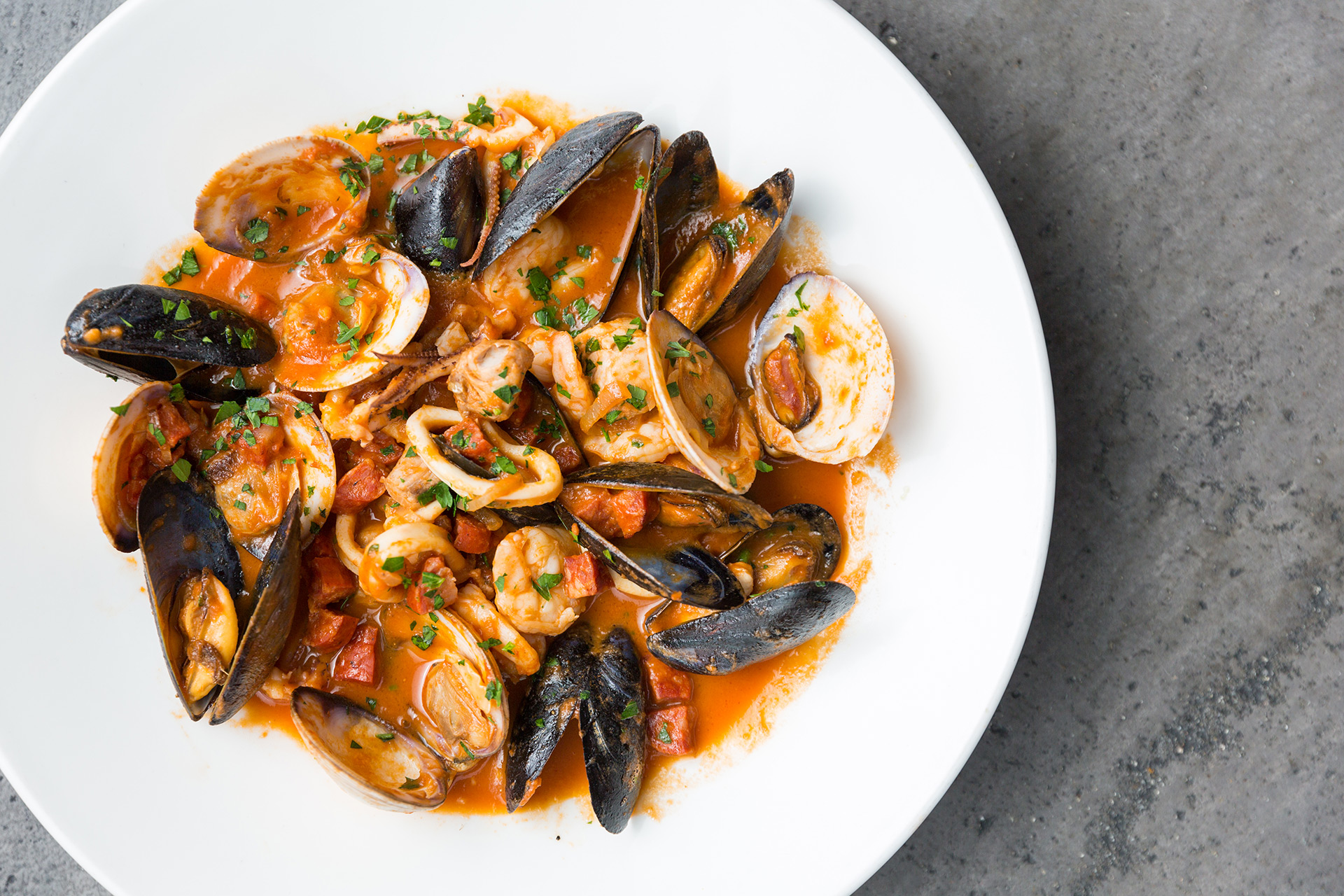 Plate of mussels, clams, shrimp and octopus in red sauce