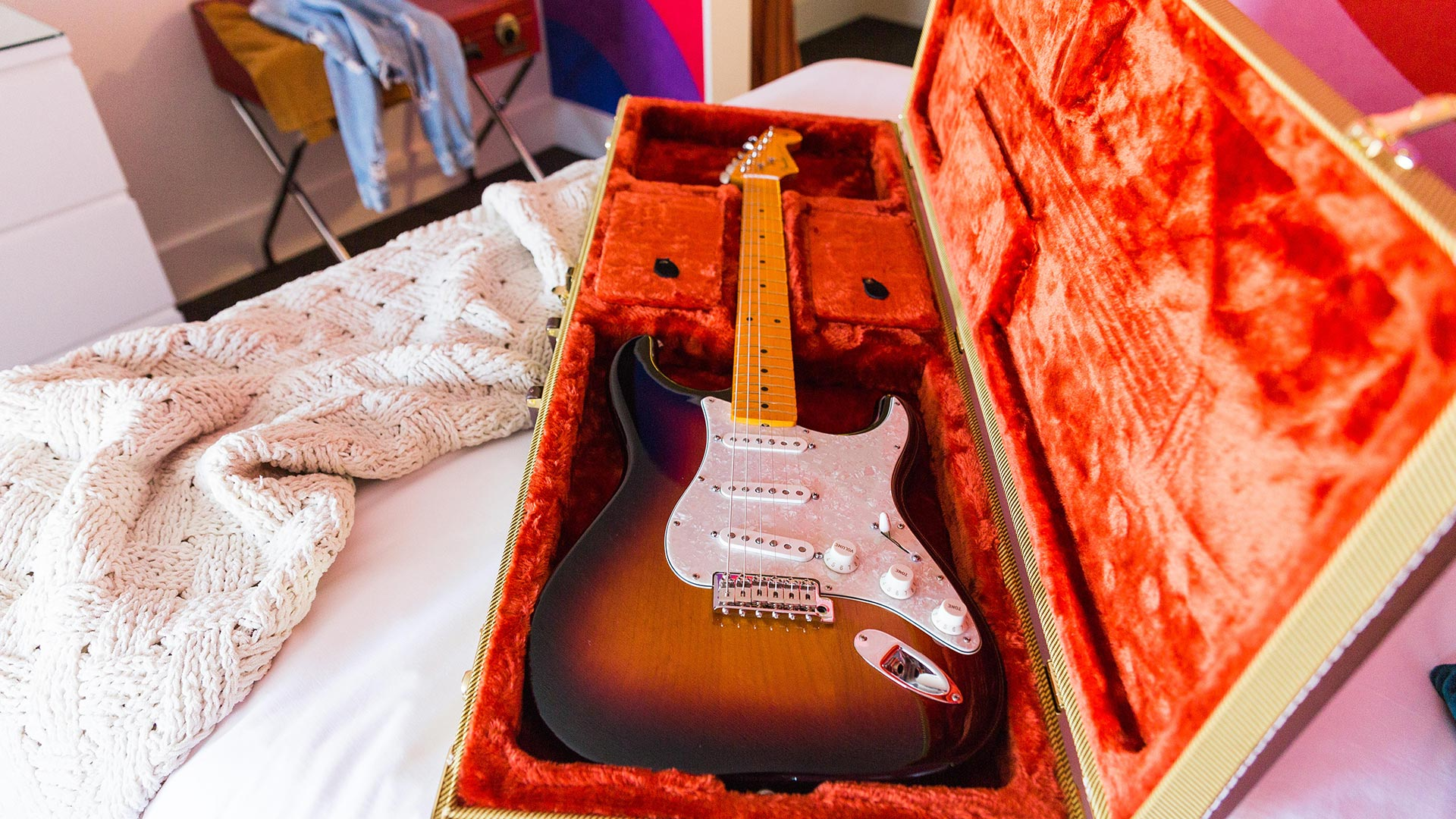 Rambler: brown electric guitar in its case on the bed