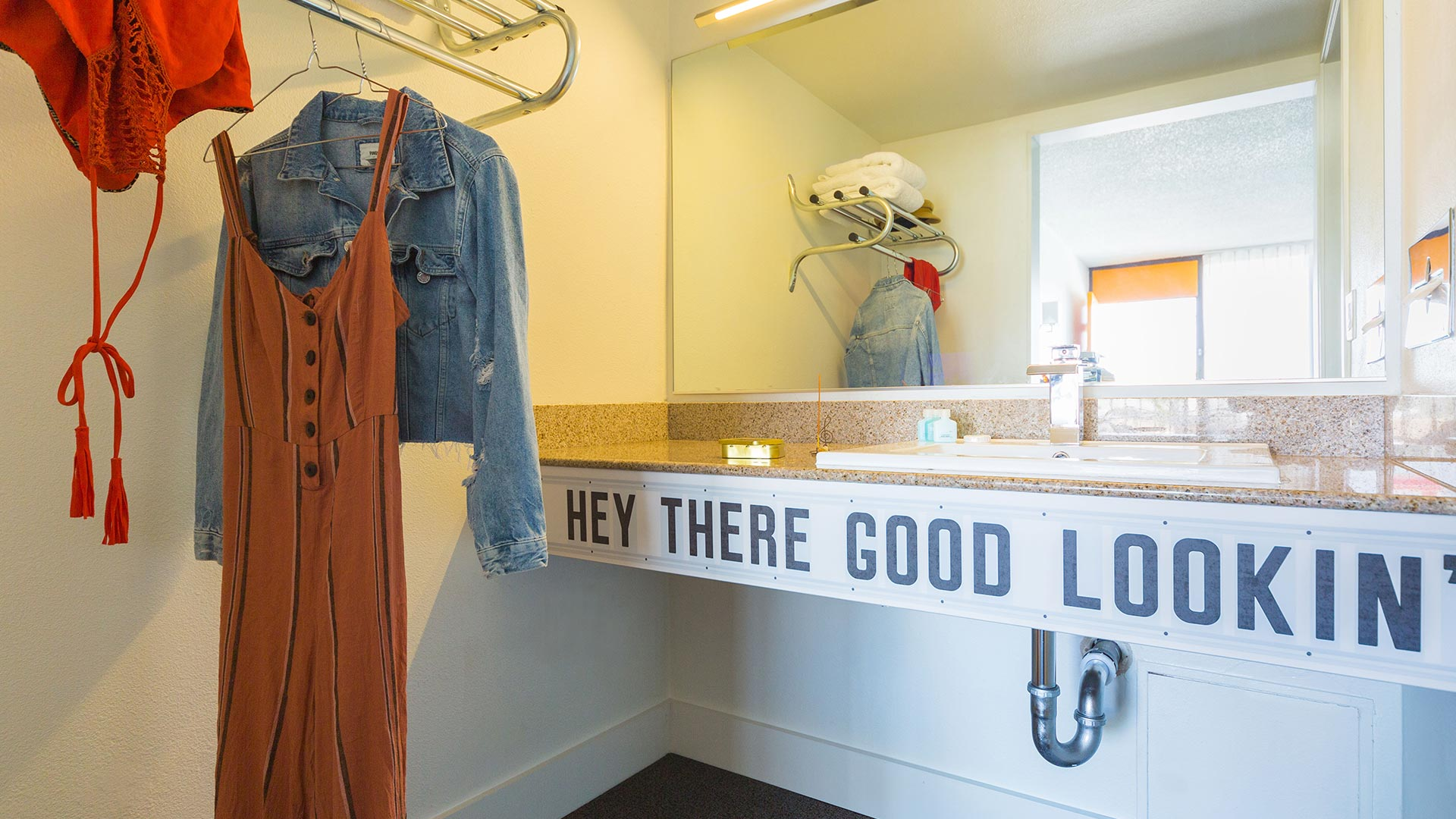 Rambler: view of bathroom sink with text Hey There Good Looking on it, clothes hanging on rack