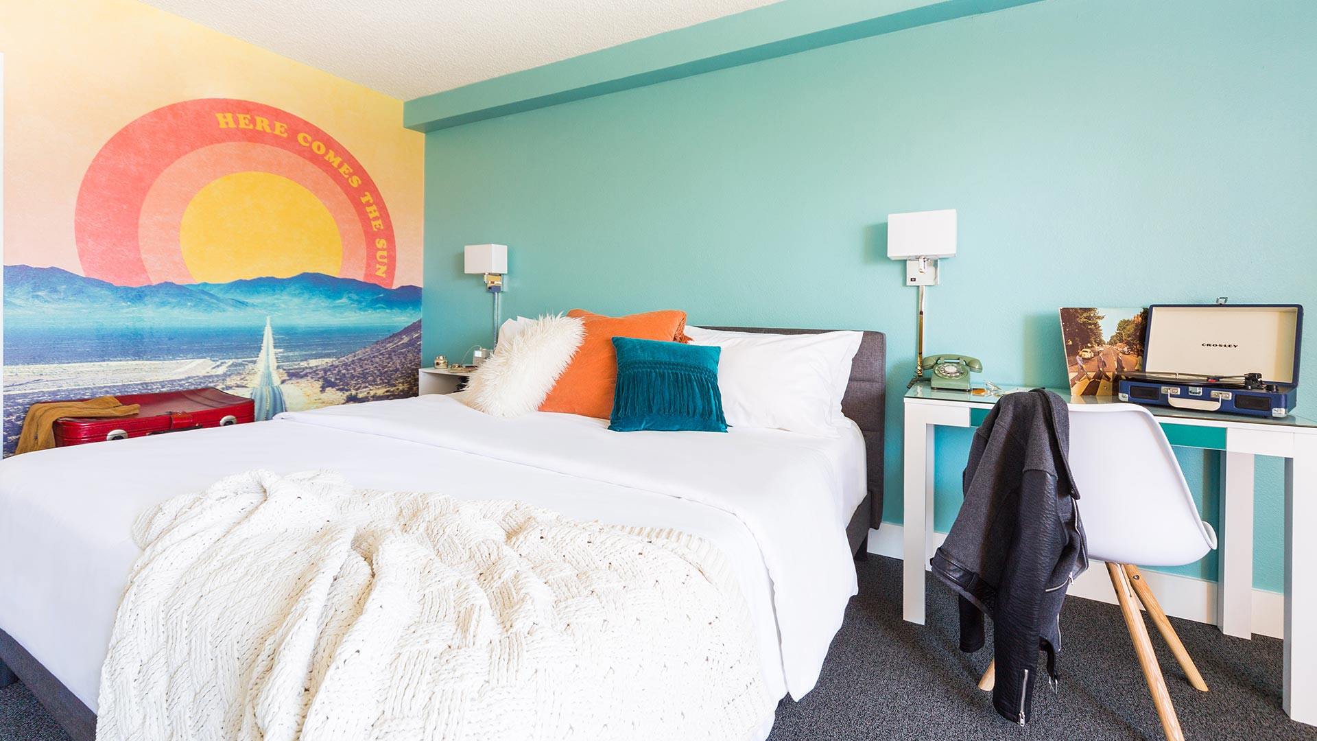 Rambler: view of King bed with Here Comes the Sun Wall graphic in view