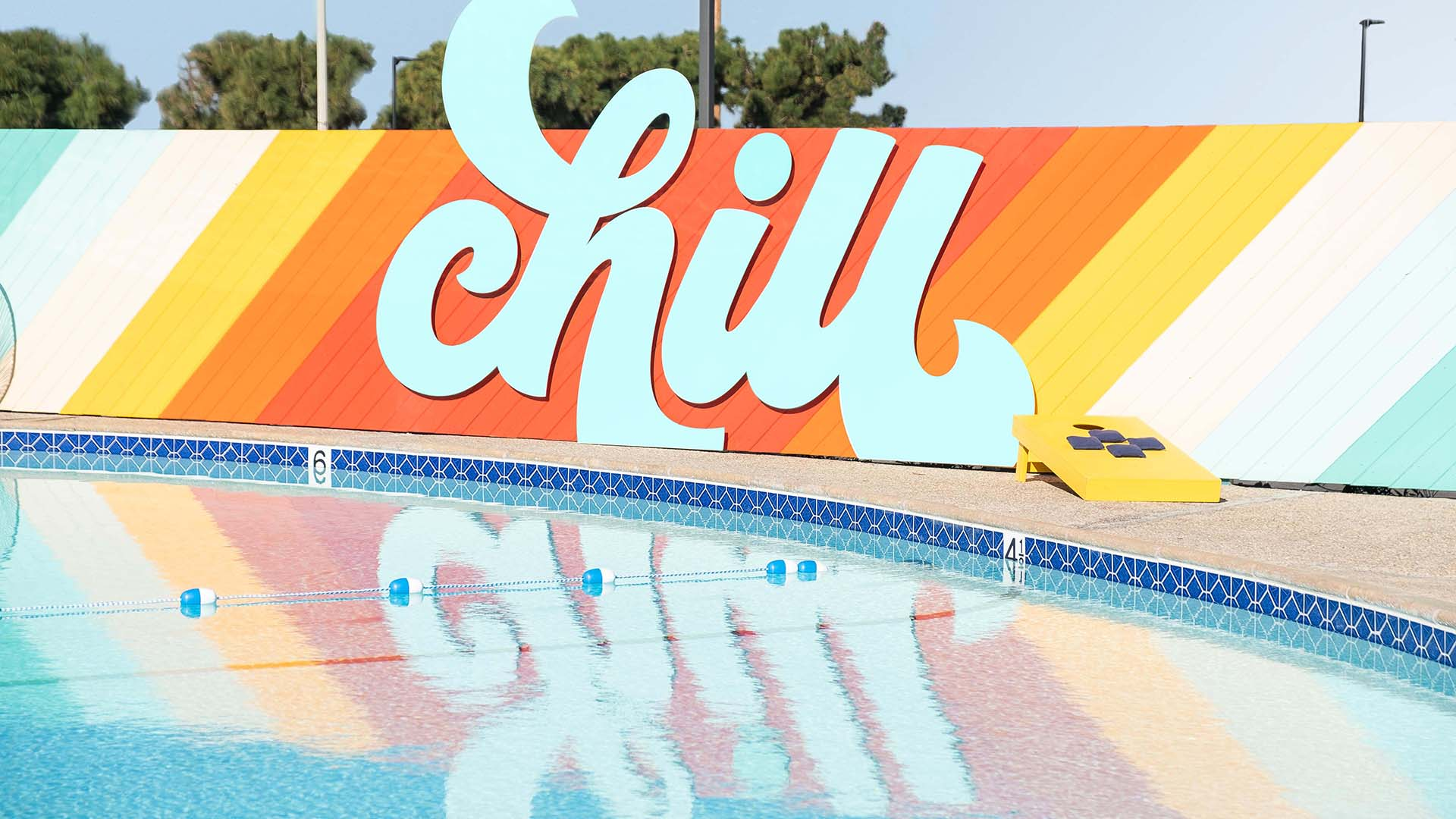 Colorful CHILL sign and its reflection on the pool